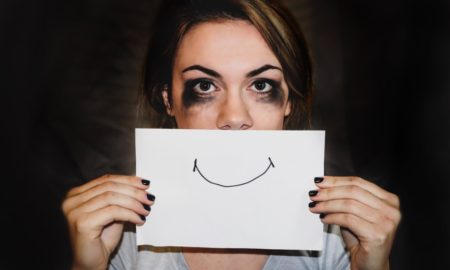 Girl Holding a fake smiley picture